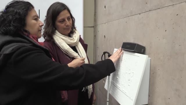 a traves de placas en relieve y audioguias las personas con dificultades de vision pueden recrear en su mente un circuito de murales callejeros en la... - personas stock videos & royalty-free footage