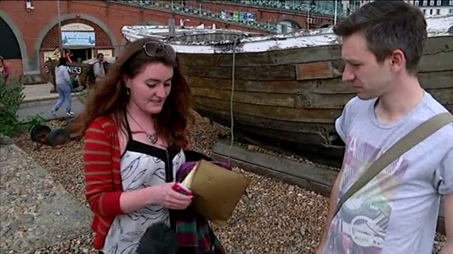 treasure hunt craze reaches uk; england: east sussex: brighton: ext sophie moorris holding envelope of money on beach and interview sot - that was... - treasure hunt stock videos & royalty-free footage