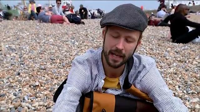 treasure hunt craze reaches uk; england: sussex: brighton: ext vox pop people on brighton beach / envelope see in hole in boat / general views boat /... - treasure hunt stock videos & royalty-free footage