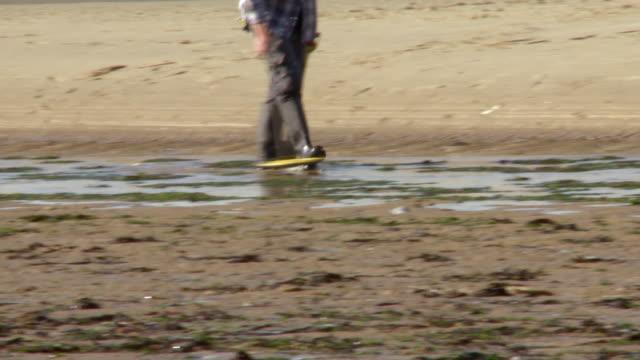 treasure hunter with metal detector on the beach - 宝探し点の映像素材/bロール