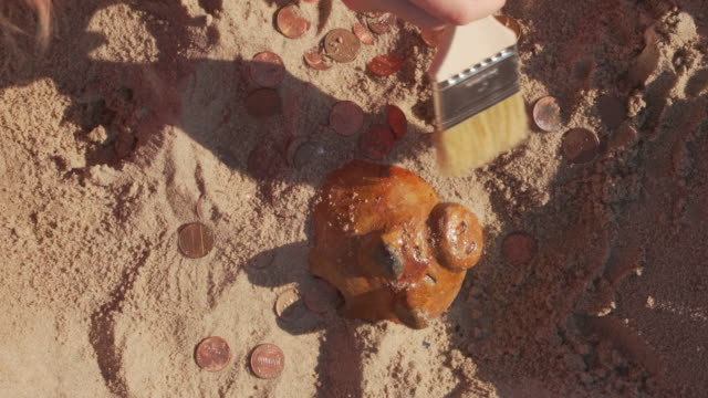 treasure hunting. kids playing archaeologists, unearthing the old piggy bank discovered hidden in the sand on a beach and picking coins. - treasure hunt stock videos & royalty-free footage