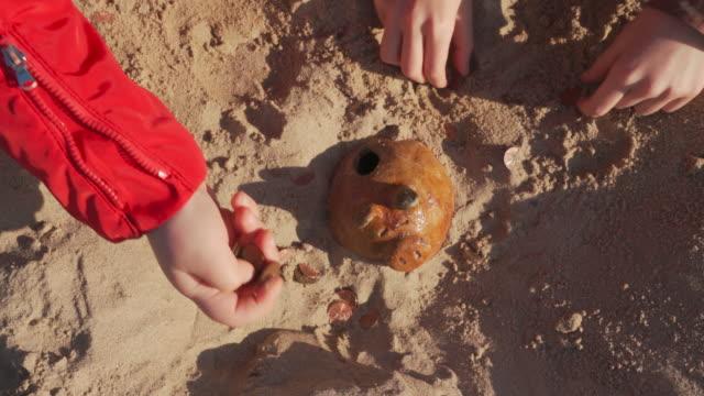 トレジャーハンティング。子供たちは考古学者を再生し、発掘は、ビーチで砂の中に隠され、コインを選ぶ古い貯金箱を発見しました。 - 宝探し点の映像素材/bロール