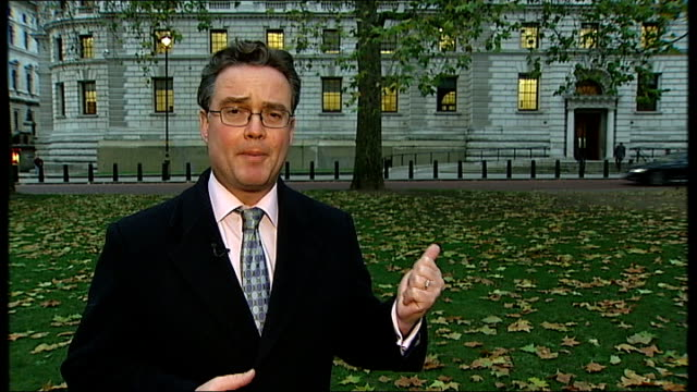 ext reporter to camera wide view hm treasury building autumn trees in foreground shots of upper windows of treasury building lights on inside tree... - financial building stock videos and b-roll footage