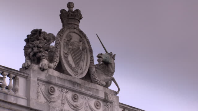 stockvideo's en b-roll-footage met treated sequence showing a british lion and unicorn crest with crown surrounding the celtic harp symbol atop dublin's custom house, republic of ireland. - snijwerk