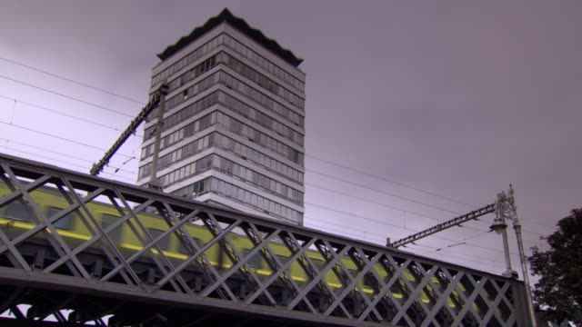 treated sequence showing a green train passing an office tower block in dublin, ireland. - office block exterior stock-videos und b-roll-filmmaterial