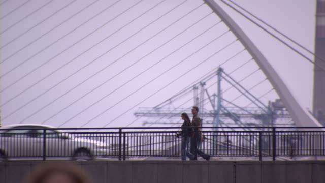 treated wide tracking shot of two people with a camera crossing the river liffey with the samuel beckett bridge in the background, dublin, ireland. - wide shot stock videos & royalty-free footage