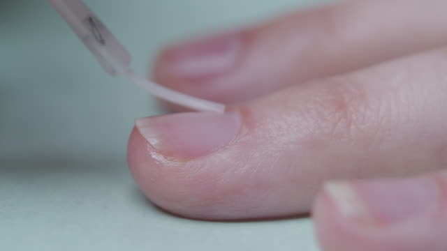 treating fingernail cuticle with nourishing oil. extreme close-up - fingernail stock videos & royalty-free footage