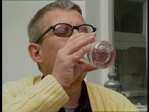 tony whitehead pouring a glass of water from kitchen tap lams whitehead sits at table with water tray of drugs prescribed to help control aids tms... - richard i of england stock videos and b-roll footage