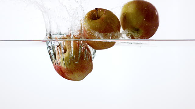 tree apples, malus domestica,  falling into water against white background, slow motion - mela video stock e b–roll