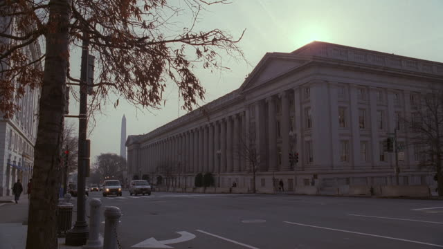 la tree branch with leaves in front of u.s. treasury building at dawn, washington monument beyond / washington, d.c., united states - finanzministerium stock-videos und b-roll-filmmaterial