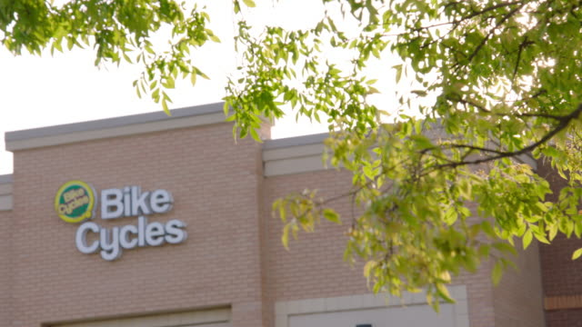 tree branches blow in the wind outside bike cycles repair shop - centro commerciale suburbano video stock e b–roll