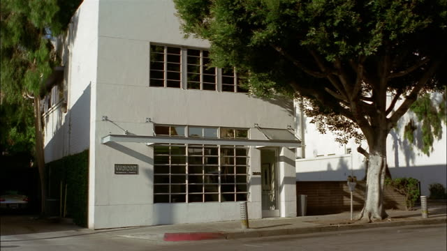 a tree grows in front of a small white two-story office building in culver city, los angeles, california. - culver city stock videos & royalty-free footage