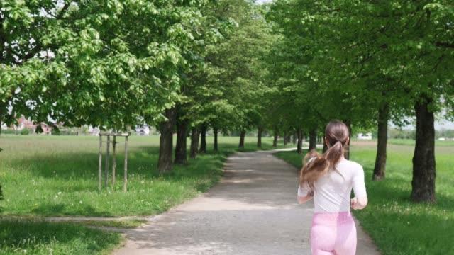 vidéos et rushes de sentier bordé par l'arbre à travers le parc est parfait pour la course - non urban scene
