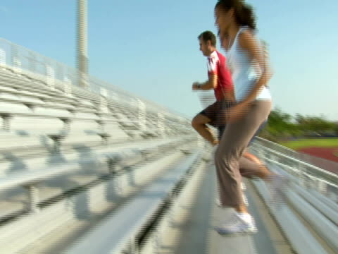 vidéos et rushes de slo mo,  pan,  la,  tree people running up on bleachers,  miami,  florida,  usa - 45 49 ans