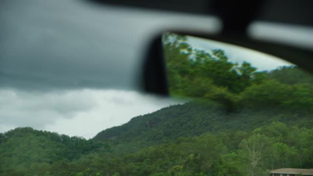 vídeos de stock, filmes e b-roll de tree reflections through the car's side mirror - vinheta