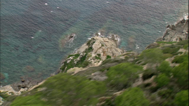 a tree-covered cliff towers over azure waters. - cote d'azur stock videos & royalty-free footage