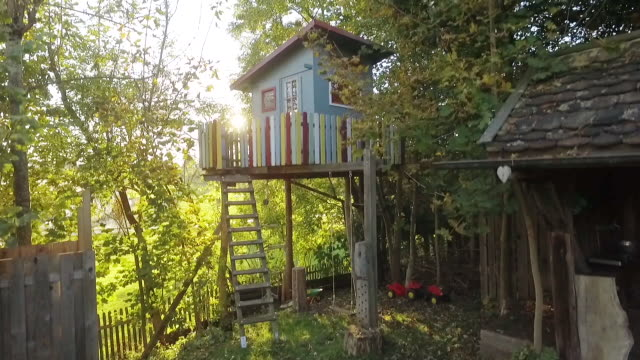 treehouse in the garden at sunset - treehouse stock videos & royalty-free footage