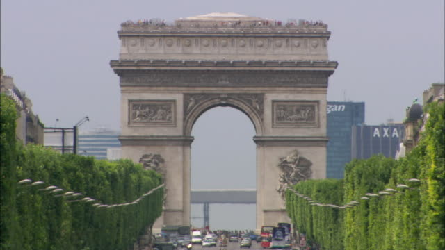 vídeos de stock, filmes e b-roll de a tree-lined avenue leads to the arc de triomphe in paris. - arco triunfal