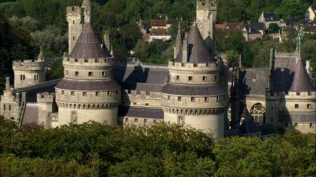 ms trees/ tu aerial over trees to chateau de pierrefonds/ pierrefonds, france - circa 12th century stock videos & royalty-free footage