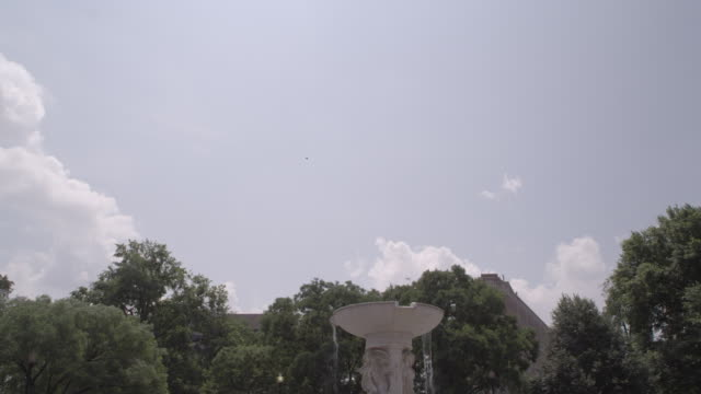 la trees and clouds hovering over the fountain at dupont circle / washington dc, united states - dupont circle stock videos & royalty-free footage