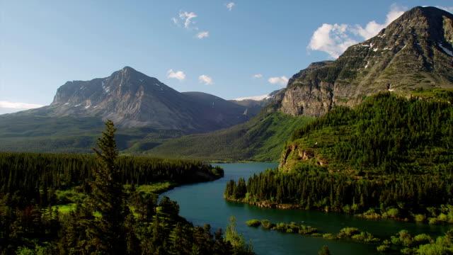 vídeos de stock, filmes e b-roll de trees and mountains surround a river running through glacier national park. - glacier national park us