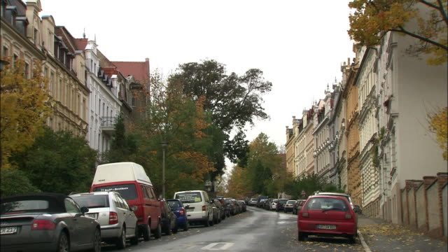 trees and parked cars line a narrow street. - parking stock-videos und b-roll-filmmaterial