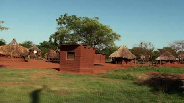 trees and short grasses surround red huts in a zambian village. - dorf stock-videos und b-roll-filmmaterial