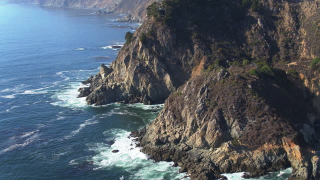trees clinging to rugged big sur cliffs - drone shot - coastline stock videos & royalty-free footage