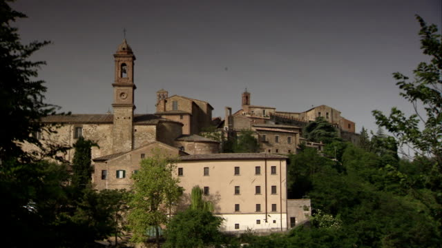 Trees frame a view of a bell tower in a village in the Tuscan countryside. Available in HD.