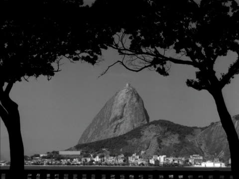 trees frame the sugar loaf mountain. 1961. - naturwunder stock-videos und b-roll-filmmaterial