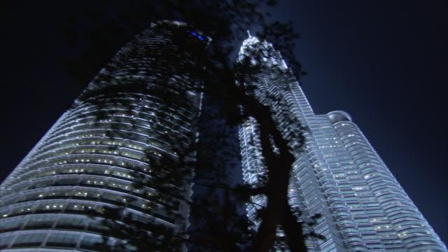 Trees line a street past illuminated skyscrapers in Kuala Lumpur at night.