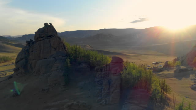 trees on rock formations by landscape with traditional houses against bright sky - ulaanbaatar, mongolia - ulan bator stock videos & royalty-free footage