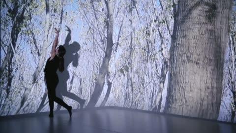 vídeos y material grabado en eventos de stock de proyección de árboles con una bailarina - realidad aumentada espacial