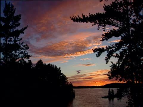 trees silhouetted against sunset over lake; minnesota - eskapismus stock-videos und b-roll-filmmaterial