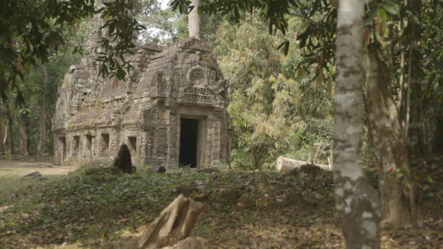 trees surround an old stone building in the angkor wat temple complex in cambodia.  - cambodia stock videos and b-roll footage