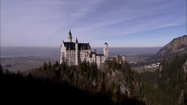 Trees surround Neuschwanstein Castle in Bavaria Germany. Available in HD.