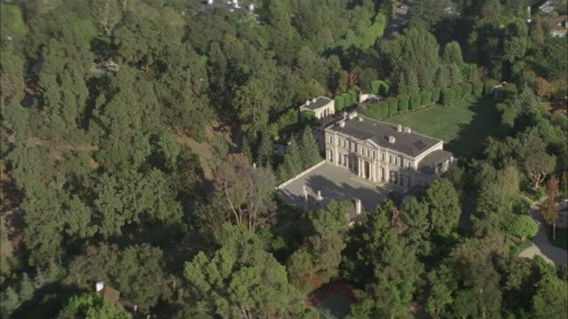 vídeos de stock e filmes b-roll de trees surround the fleur de lys mansion in beverly hills. - riqueza