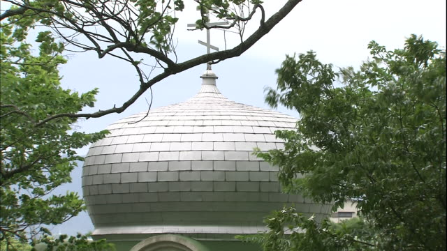 trees sway around the onion dome of a russian orthodox church in nagasaki's inasa international cemetery. - onion dome stock videos and b-roll footage