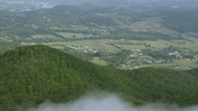 WS TU AERIAL POV Treetop over Great Smoky Mountains with town in background / Carter County, Tennessee, United States
