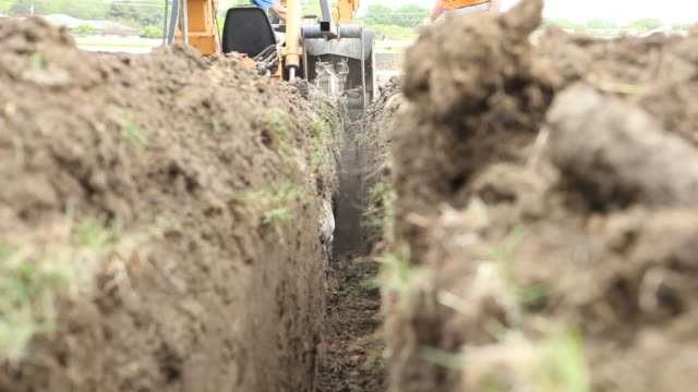 trench digger slicing soil for an electric line - trench stock videos & royalty-free footage
