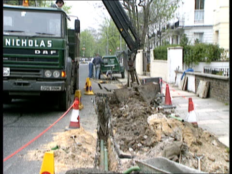 trench in road / lorry removing rubble/ cable in trench/ ground shot of trench tony currie cable authority seated at desk flicking through programmes... - cable tv stock videos & royalty-free footage