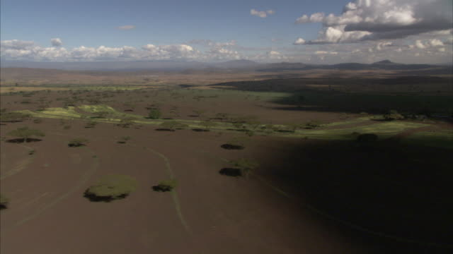 vídeos de stock, filmes e b-roll de a trench runs across plains in kenya's great rift valley. - geologia