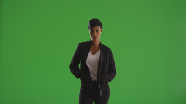 trendy black woman posing with hands in jacket pockets on green screen - jacket stock videos & royalty-free footage