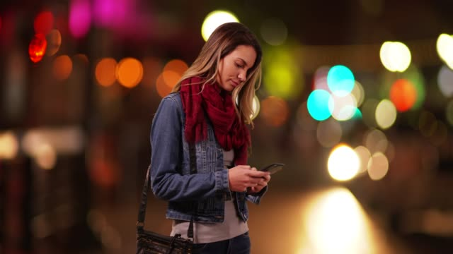 vídeos de stock, filmes e b-roll de trendy caucasian millennial girl messaging on smartphone downtown at night - jaqueta jeans