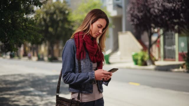 vídeos de stock, filmes e b-roll de trendy caucasian millennial girl messaging on smartphone downtown during the day - jaqueta jeans
