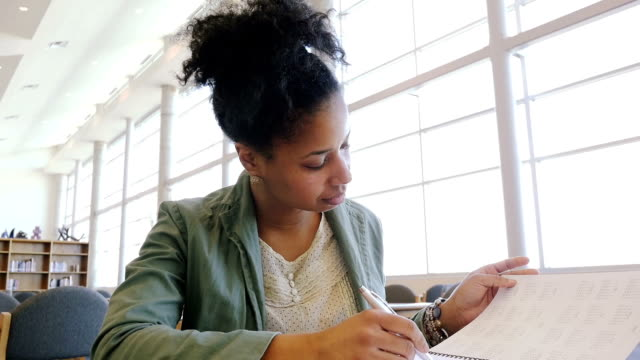 Trendy female adult student writing in notebook during study session in college library