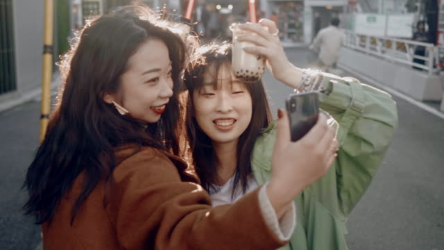trendy japanese female friends taking selfies with bubble tea in the sunset - city life stock videos & royalty-free footage