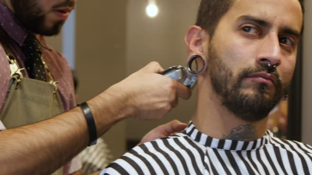 trendy man getting his haircut by barber - electric razor stock videos and b-roll footage
