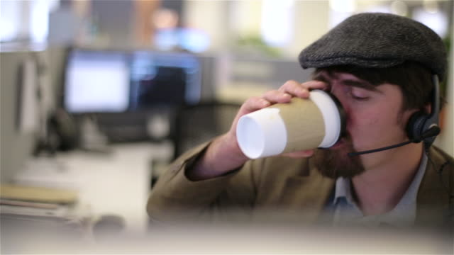 Trendy office worker in cubicle with headset sips coffee