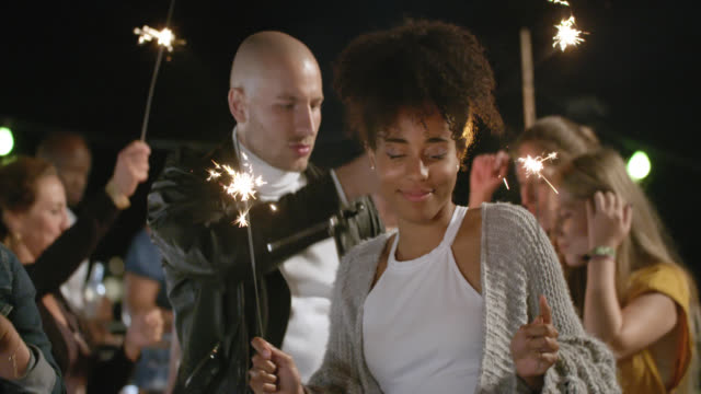 vidéos et rushes de trendy, stylish crowd of multicultural people celebrating, partying and dancing together with burning sparklers on roof deck while night. - garden party